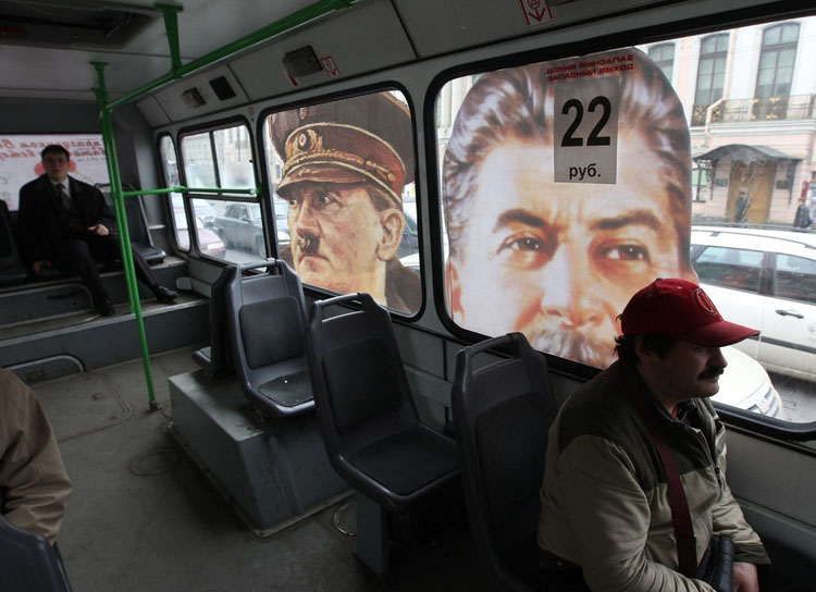 People sit in a bus with a portrait of the Soviet dictator Josef Stalin in the centre of St.Petersburg